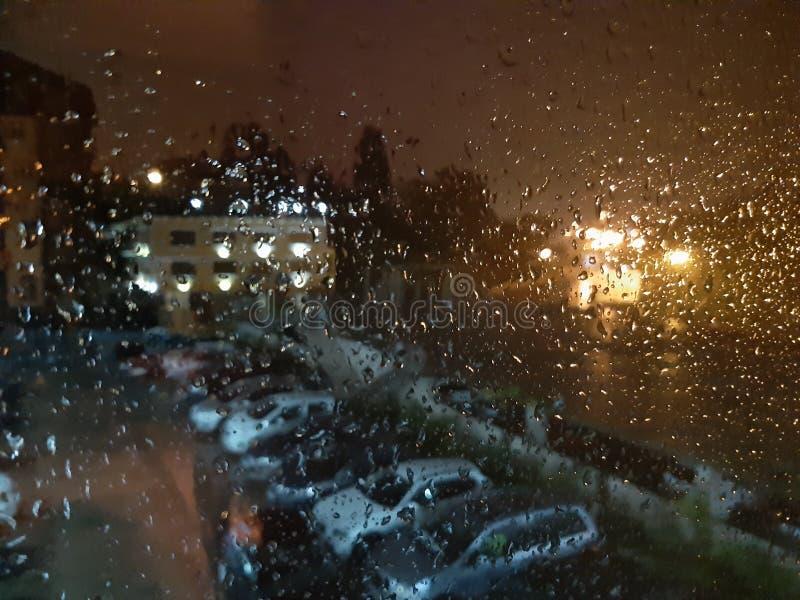 湿晴雨表在反对庭院的背景的晚上有汽车的 免版税库存图片