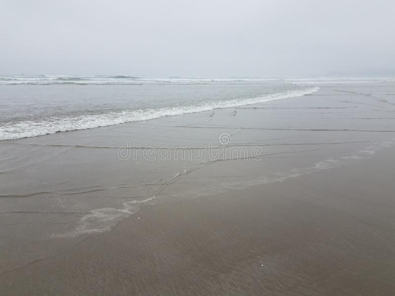 湿横渡在海滩的沙子和波浪 免版税库存图片