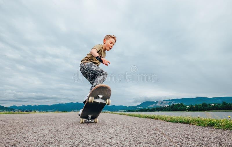 年轻溜冰板者做与滑板的把戏 免版税库存图片