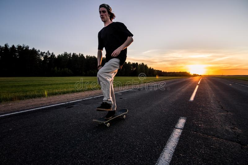 溜冰板者在空的路乘坐在美好的日落 免版税库存照片