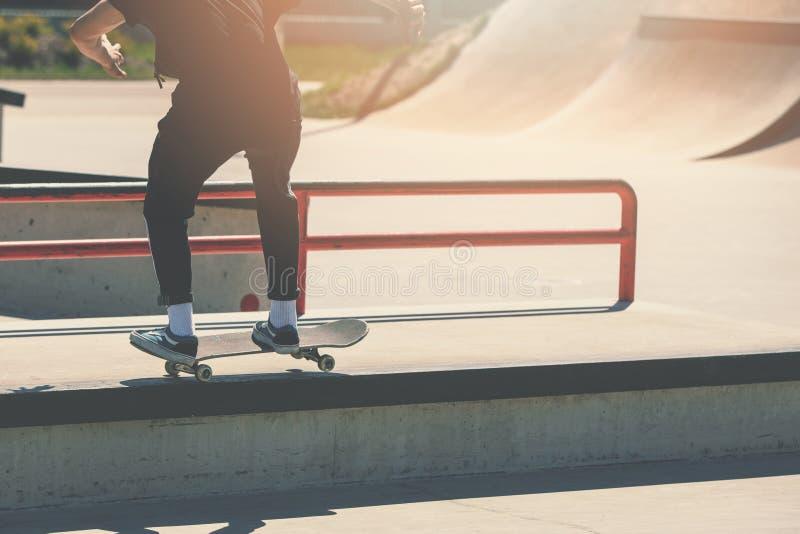 溜冰板运动-做把戏的溜冰者男孩在skatepark 免版税库存照片
