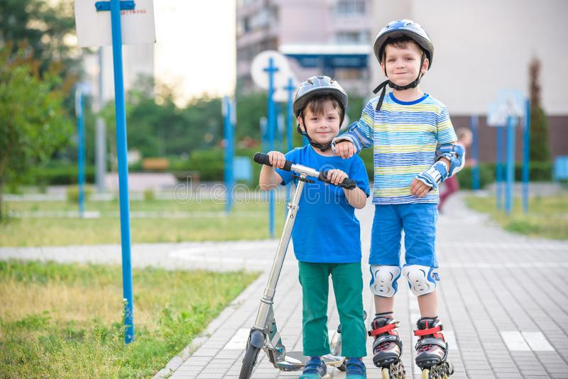 溜冰鞋和他的兄弟姐妹兄弟的两个孩子男孩在公园包裹的滑行车的 佩带安全路辗的孩子保护垫 免版税库存图片
