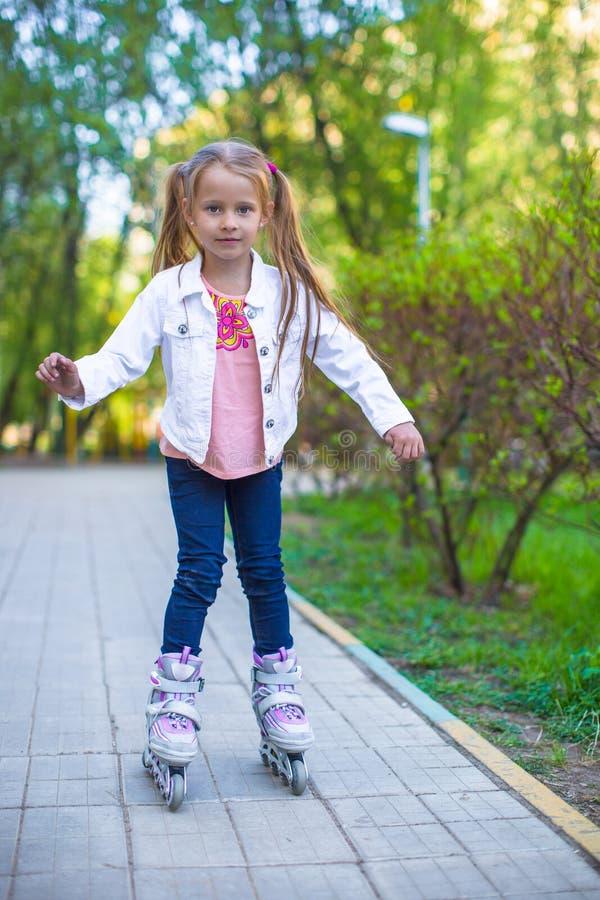 溜冰鞋的可爱的小女孩在公园 免版税图库摄影