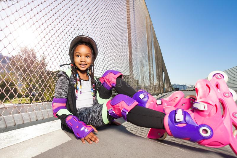 溜冰鞋的女孩坐公园地板  免版税库存照片