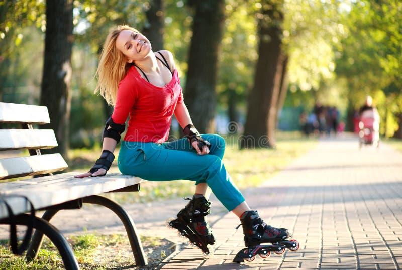 溜冰鞋的美丽的少妇坐公园长椅 免版税库存照片