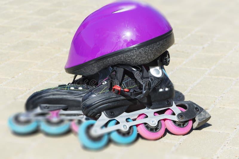 溜冰鞋,在路面瓦片背景的盔甲 库存图片