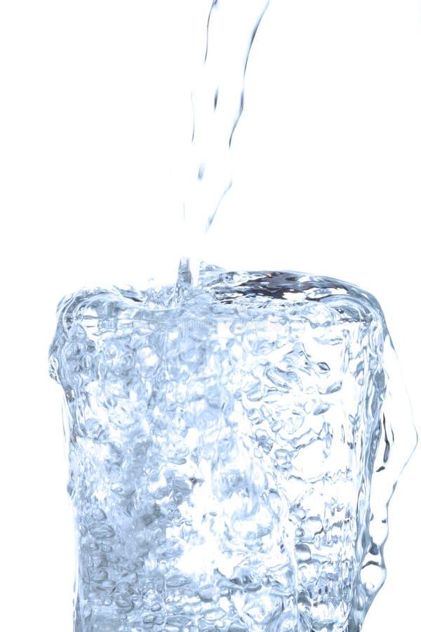 溢出入在白色的玻璃的倾吐的饮用水 免版税库存照片