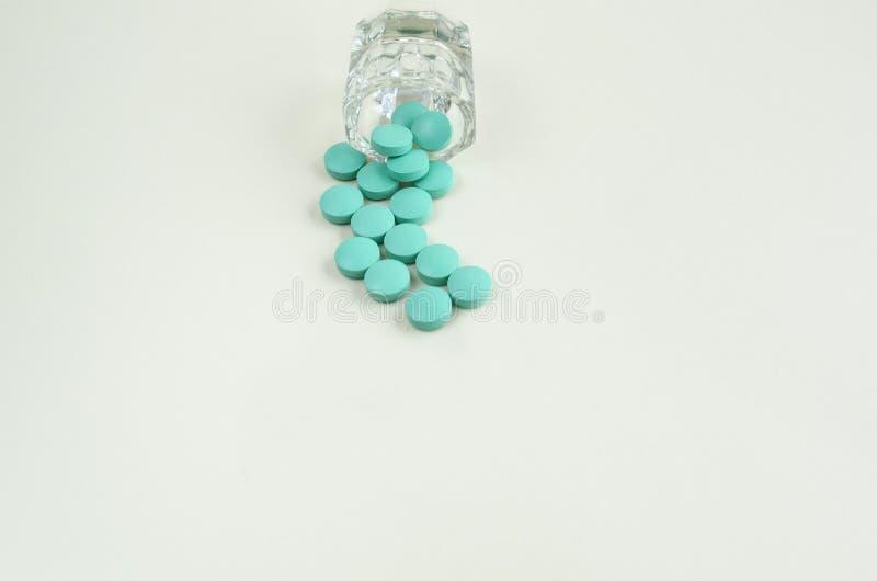 溢出在白色背景的药瓶外面的药片 r 图库摄影