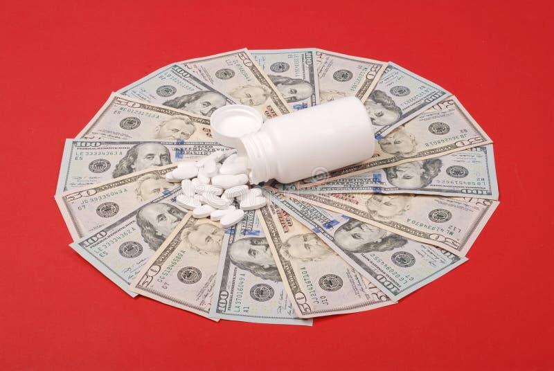 溢出在金钱的药瓶外面的药片,以圈子的形式 免版税库存照片