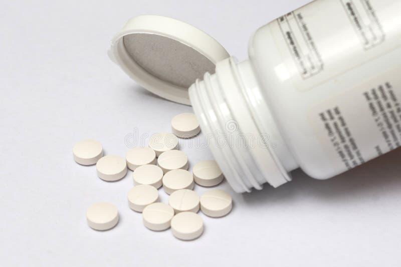 溢出形式的白色药片它的瓶 图库摄影