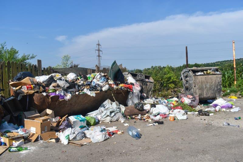 溢出的垃圾箱在城市 垃圾容器在地板上溢出与垃圾和投掷 未倒空容器 库存图片