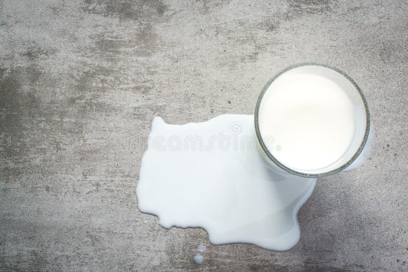 溢出的牛奶和一杯在具体桌上的牛奶 免版税库存照片