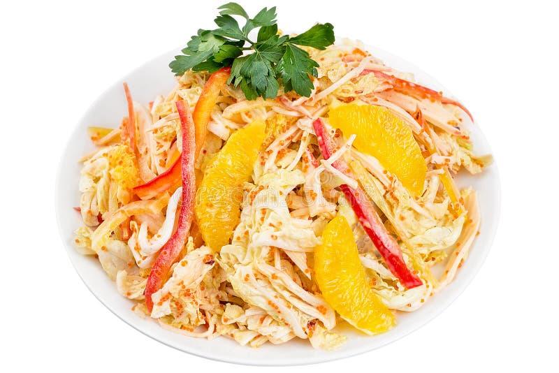 滋补菜沙拉的大角度看法与橙色切片的,服务在一块白色板材 查出 免版税库存照片