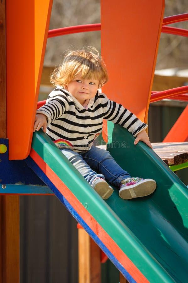 滑下来儿童的幻灯片的逗人喜爱的矮小的小孩女孩 免版税库存照片
