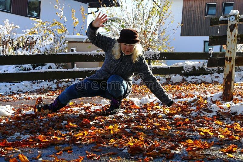 滑倒的风险在秋天和冬天 妇女在湿,光滑的叶子滑倒了 库存图片