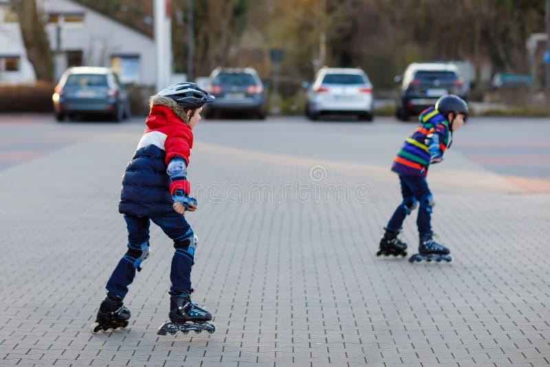 滑冰与路辗的两个小孩男孩在城市 愉快的孩子、兄弟姐妹和最好的朋友保护安全的 库存图片