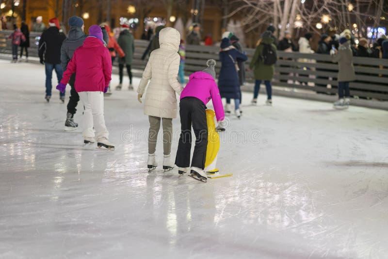 滑冰回到我们的人 与滑冰在城市公园的孩子的家庭度假,室外冬天活动 免版税库存照片