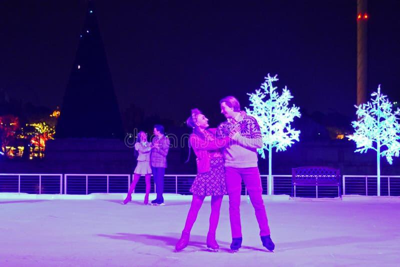 滑冰在冰的可爱的夫妇的在圣诞节展示在国际推进地区 免版税图库摄影