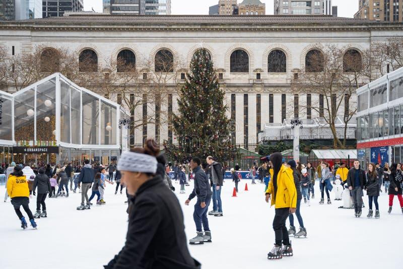 滑冰在圣诞树下 免版税库存照片