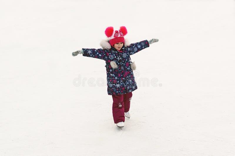 滑冰在滑冰场的可爱的小女孩户外 免版税库存照片