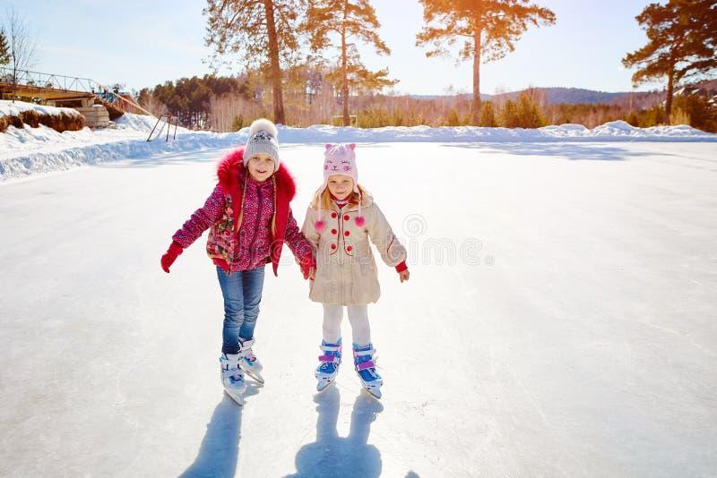 滑冰在滑冰场的愉快的孩子户外 体育和一种健康生活方式 滑稽的孩子,他们是姐妹和女朋友 免版税图库摄影
