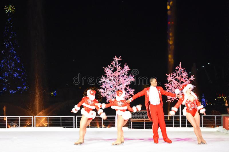 滑冰在滑冰场的艺术家在假日树背景的圣诞节展示在国际推进地区 图库摄影