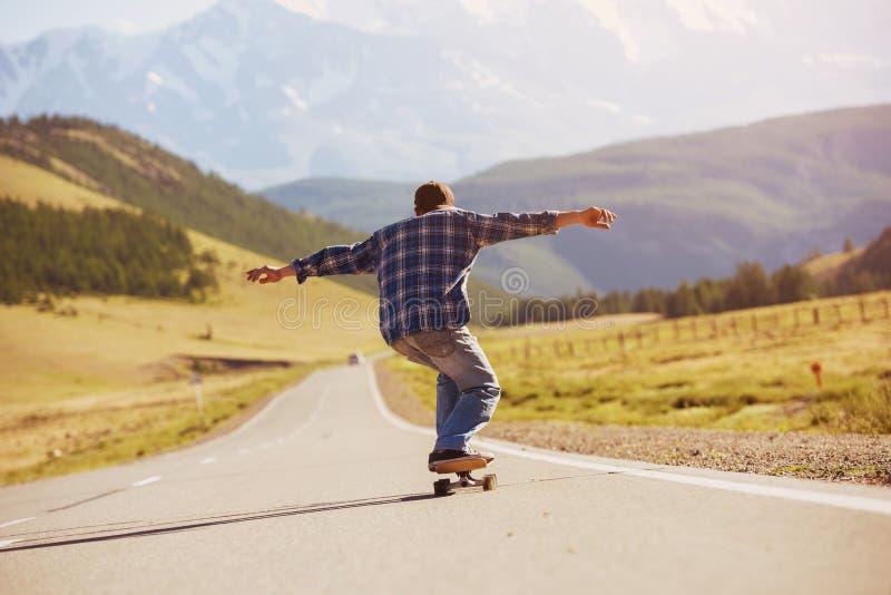 滑冰在longboard平直的山路的人 免版税库存照片