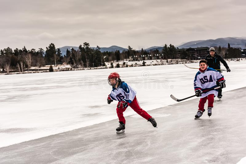 滑冰在Mirror湖的年轻曲棍球滑雪者 库存照片