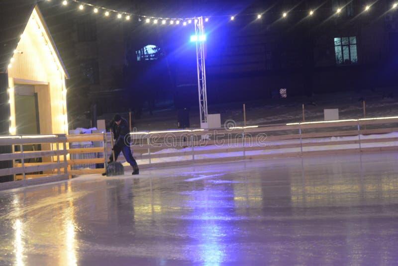 滑冰场工作者在滑冰场冰处理机以后计数多雪,冰冷的大量的遗骸从冰的 免版税库存图片