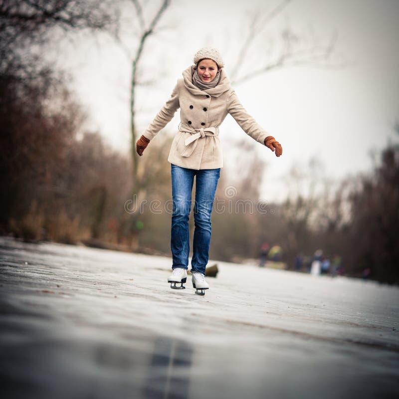 滑冰户外在池塘的少妇 免版税库存图片