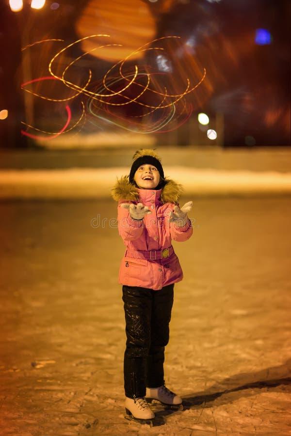 滑冰逗人喜爱的女孩 儿童滑冰场的冬天户外 库存照片