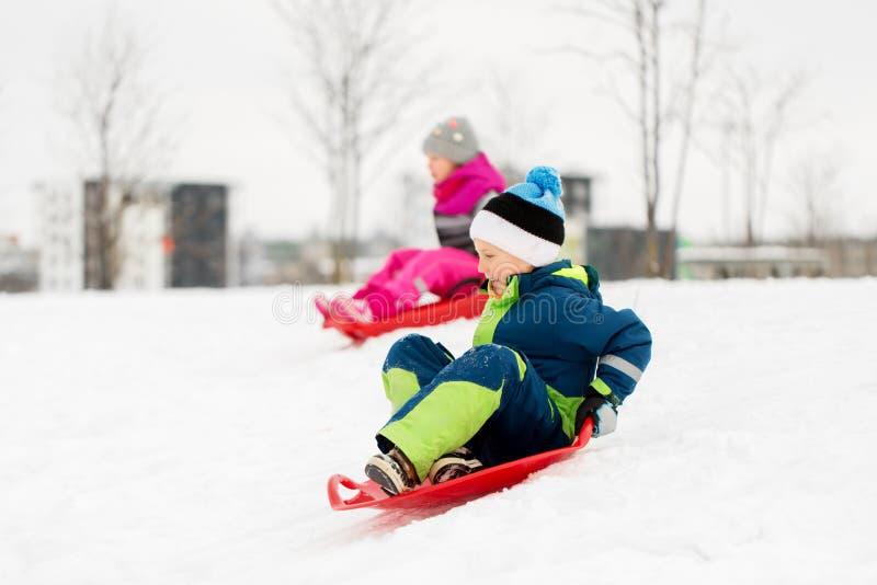 滑在雪撬的孩子下来在冬天下雪小山 免版税图库摄影