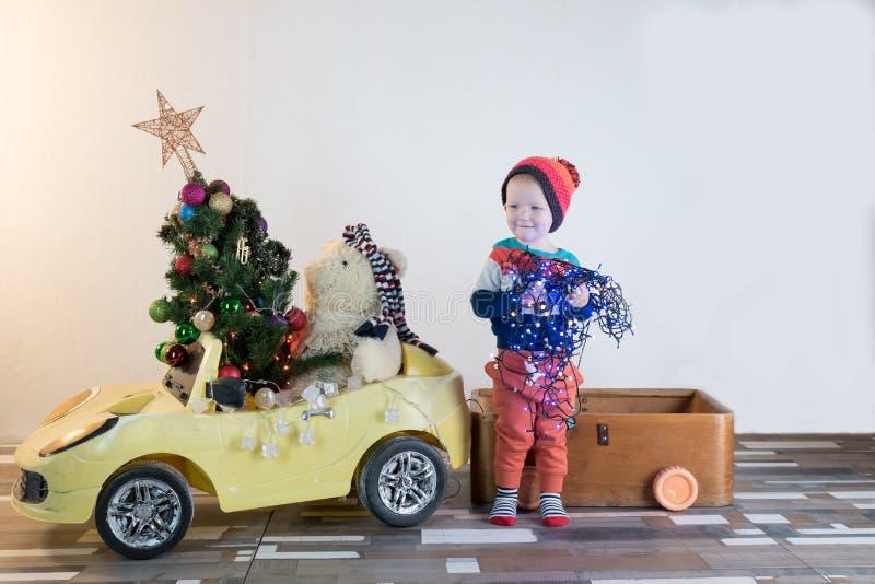 滑稽一点微笑哄骗驾驶有圣诞树的玩具汽车 愉快的孩子以颜色时尚给带来被砍成的xmas树穿衣从 库存照片