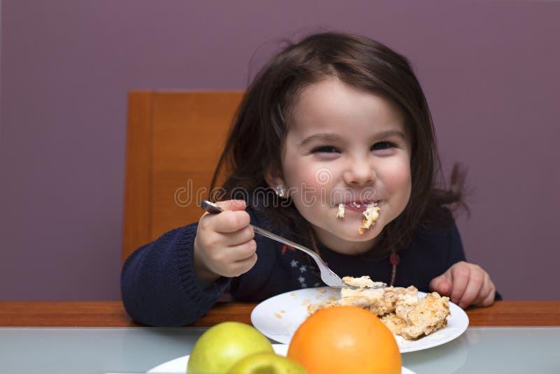 滑稽女孩吃 她坐在桌上 免版税库存照片