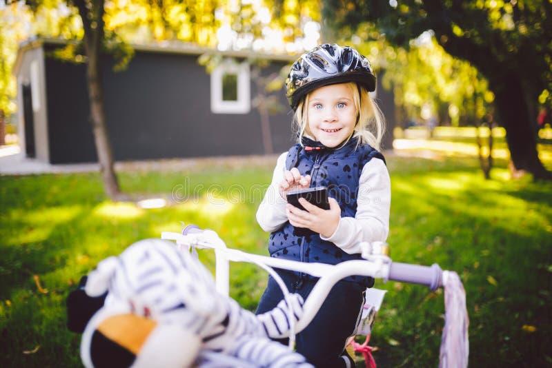 滑稽的一件自行车盔甲的儿童白种人女孩金发碧眼的女人在有一个篮子的一辆紫色自行车附近一棵绿色草坪草的公园外 库存图片