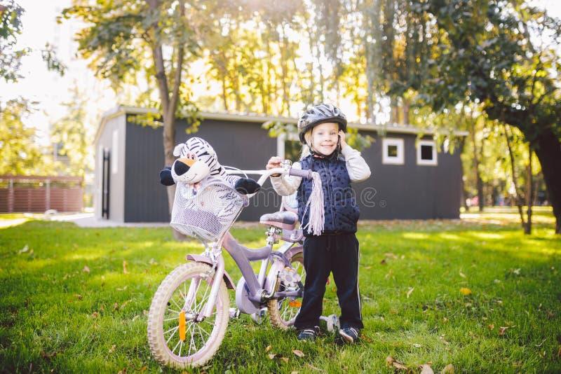 滑稽的一件自行车盔甲的儿童白种人女孩金发碧眼的女人在有一个篮子的一辆紫色自行车附近绿色 免版税库存照片