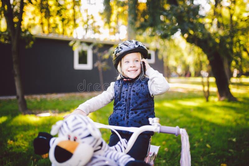 滑稽的一件自行车盔甲的儿童白种人女孩金发碧眼的女人在有一个篮子的一辆紫色自行车附近绿色 免版税图库摄影