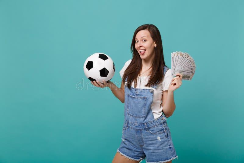 滑稽的与足球的年轻女人足球迷支持喜爱的队,金钱在美元钞票,现金金钱爱好者  免版税图库摄影