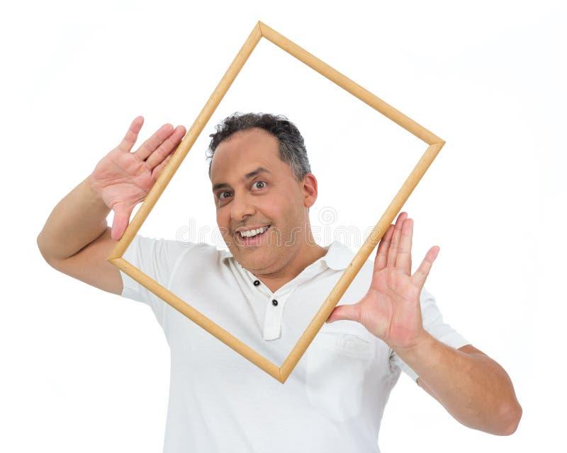 滑稽的人在面孔附近拿着框架框架 他超重并且是 库存图片