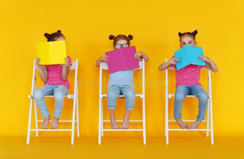 滑稽的儿童女孩在色的黄色背景读了书 免版税库存照片