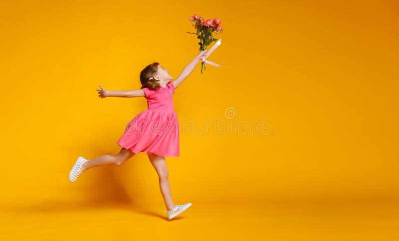 滑稽的儿童女孩跑并且跳与花花束在颜色的 免版税库存照片