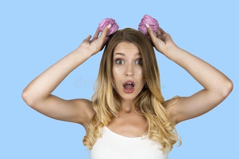 滑稽的可爱的女孩用在头被隔绝的蓝色背景附近的杯形蛋糕 免版税库存图片