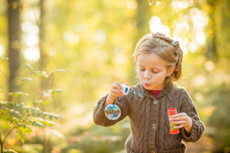 滑稽的可爱的小女孩吹的肥皂泡画象  黄色被编织的外套的逗人喜爱的白肤金发的蓝眼睛的女孩在 免版税库存图片