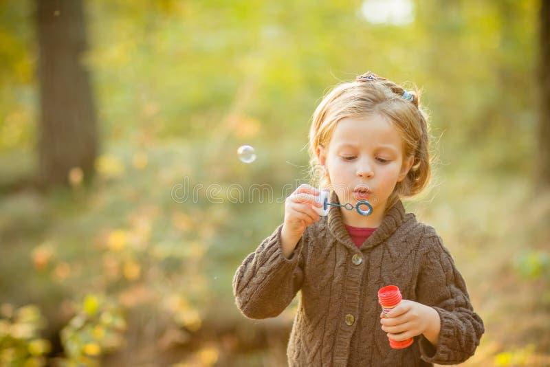 滑稽的可爱的小女孩吹的肥皂泡画象  黄色被编织的外套的逗人喜爱的白肤金发的蓝眼睛的女孩在 图库摄影