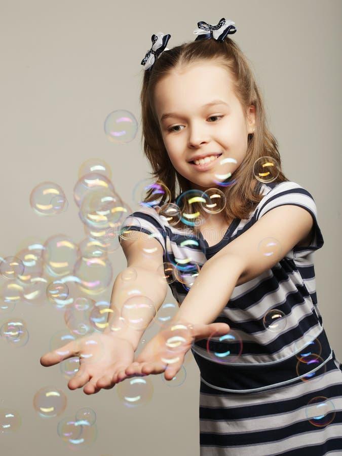 滑稽的可爱的小女孩witj肥皂泡 图库摄影
