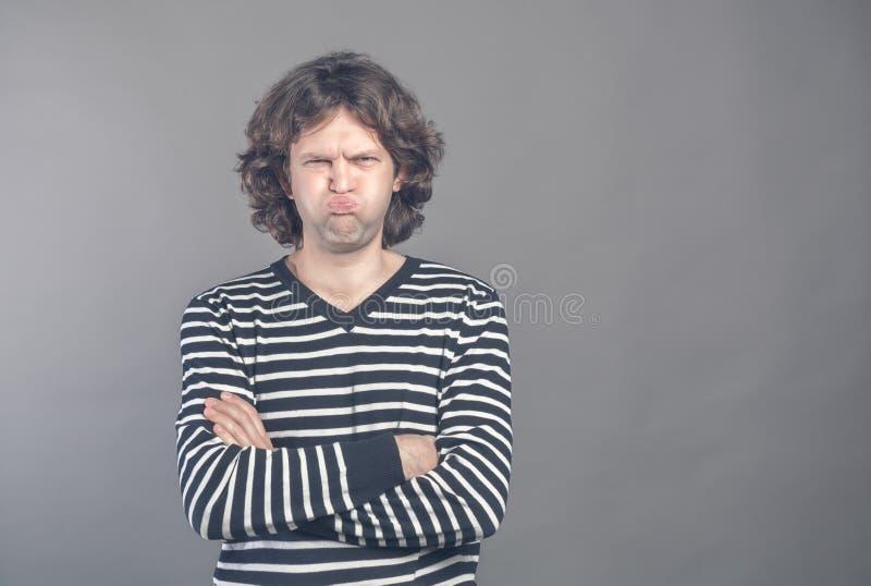 滑稽的可笑的人噘嘴嘴唇,并且面颊做恼怒的鬼脸,在整天工作以后的foolishes 有笨拙的无知的男性书呆子 免版税库存照片