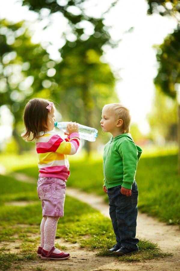 滑稽的喝矿泉水的男孩和女孩在公园 免版税图库摄影