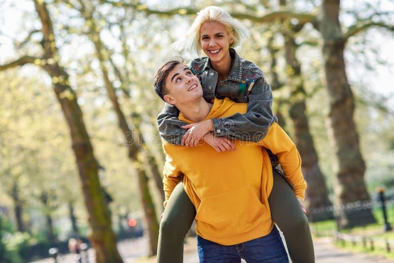 滑稽的夫妇在都市公园 运载他的背上的男朋友女朋友 库存图片