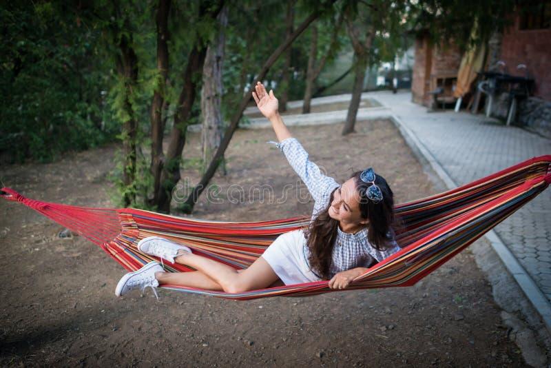 滑稽的女孩在一个红色明亮的吊床在并且起来她的手并且获得乐趣 库存图片