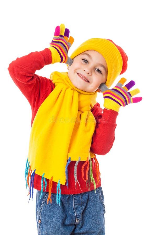 滑稽的女孩在五颜六色的冬天给显示笑话穿衣 库存照片